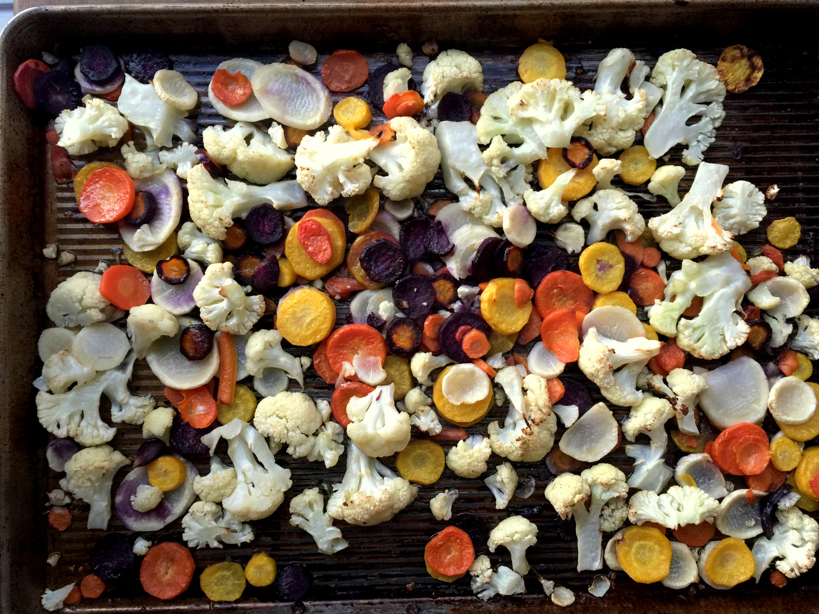 Roasted cauliflower and carrots on baking sheet